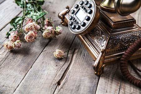 grabado antiguo: Teléfono negro de la vendimia vieja rotativa y un ramo de rosas sobre fondo de madera