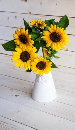 Zonnebloemen in een vaas op een rustieke, grijze achtergrond