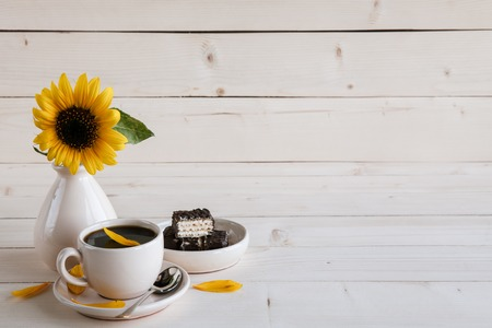 green life: sunflower and a cup of coffee on a wooden background Stock Photo