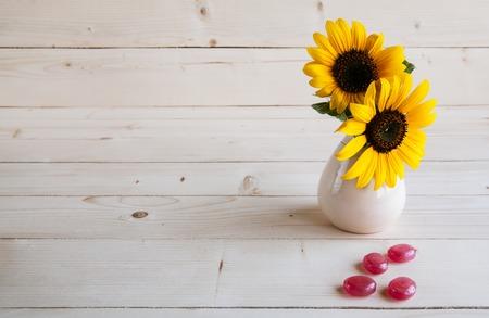 zonnebloem op een houten achtergrond met rood snoep
