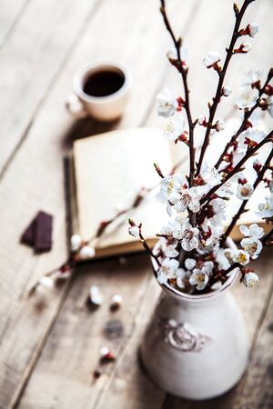 Open vintage book with blossom branch of cherry-tree on  wooden table with a beautiful vintage vase photo