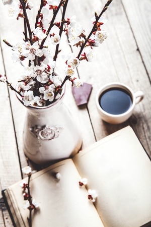 cherrytree: Open vintage book with blossom branch of cherry-tree on  wooden table with a beautiful vintage vase. a cup of coffee Stock Photo
