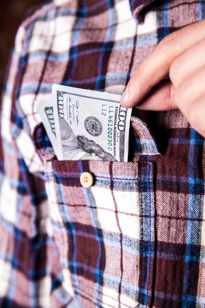 cashing: hundred american dollars in the pocket of shirt Stock Photo