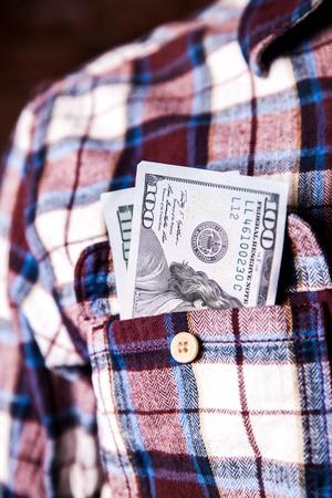 remuneraciones: cien d�lares americanos en el bolsillo de la camisa Foto de archivo