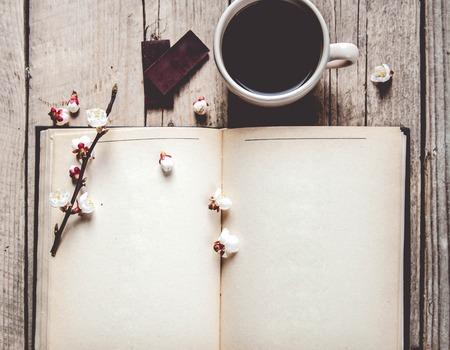 Open uitstekend boek met bloesem tak van de kersenboom op houten tafel Stockfoto