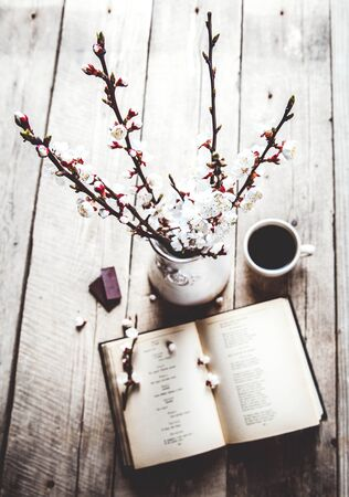 bible flower: Open vintage book with blossom branch of cherry-tree on  wooden table with a beautiful vintage vase. a cup of coffee Stock Photo