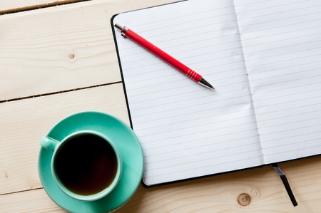 Open a blank white notebook, pen and cup of tea on the desk photo