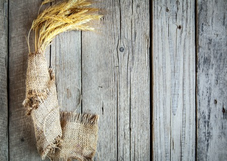 Tarwe oren op de houten tafel. Schoof van tarwe op hout achtergrond. Oogst begrip