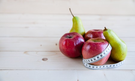 peer en appel op de houten achtergrond, de vorm van het lichaam Stockfoto