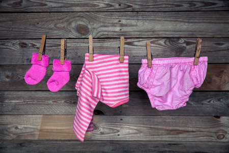 clothes hanging: Baby clothes hanging on clothesline, on wooden background