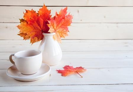 De esdoornbladeren van de herfst bundelen bos in vaas op oude houten achtergrond Stockfoto