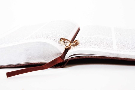 "vow: Two wedding rings on a bible, open to Corinthians Chapter 13, ""The Gift of Love"""