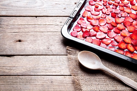 fruit. sliced Strawberry with wooden spoons baking on a dark metal plate in oven. wood background Imagens