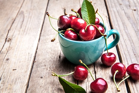 Cherries in the beautiful turquoise cup on wooden table, macro background, fruits, berries