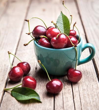 cherry: Cherries in the beautiful turquoise cup on wooden table, macro background, fruits, berries
