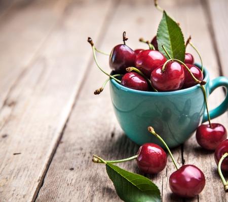cereza: Cerezas en la hermosa copa de color turquesa en la mesa de madera, fondo macro, frutas, bayas