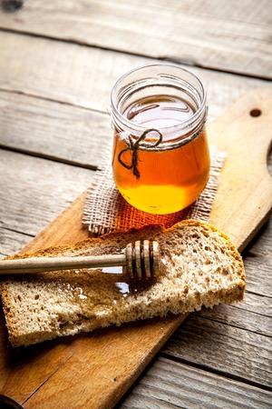 Honing in een pot, sneetje brood, tarwe en melk op een oude vintage planken houten tafel van boven. Landelijke of rustieke stijl ontbijt concept. Achtergrond lay-out met vrije tekst ruimte.