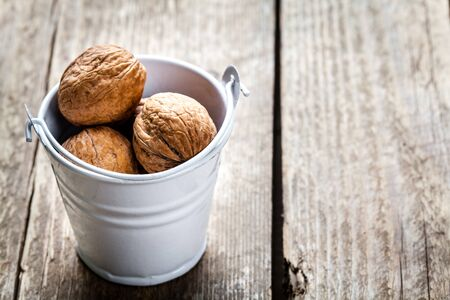 un healthy: pecan nuts in a bucket on a wooden background