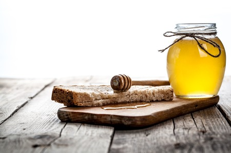 Honey in a jar, slice of bread, wheat and milk on an old vintage planked wood table from above. Rural or rustic style breakfast concept. Background layout with free text space.