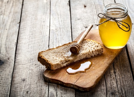 petit dejeuner: Miel dans un bocal, tranche de pain, le bl� et le lait sur une vieille table en bois vintage � partir de planches ci-dessus. Petit-d�jeuner de style notion rural ou rustique. Mise de fond avec l'espace libre de texte.
