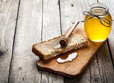 desayuno: Miel en un frasco, rebanada de pan, el trigo y la leche en una vieja mesa de madera tablones vendimia desde arriba. Rural o r�stico concepto de desayuno estilo. La disposici�n del fondo con el espacio de texto libre.