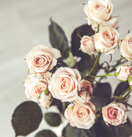 Mooi boeket van perzik rozen in vintage vaas op een zwarte achtergrond