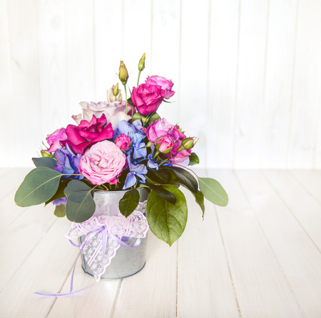 bouquet: flowers. bouquet of roses in a bucket on a white wooden background Stock Photo
