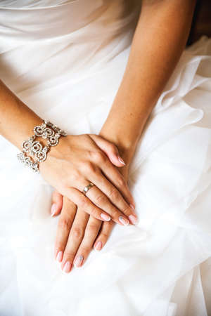 french manicure: Hands of the bride on a wedding dress. French manicure. Wedding Fashion