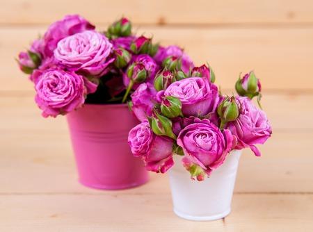 ramo de flores: Rosas de color rosa en un florero sobre fondo de madera Foto de archivo