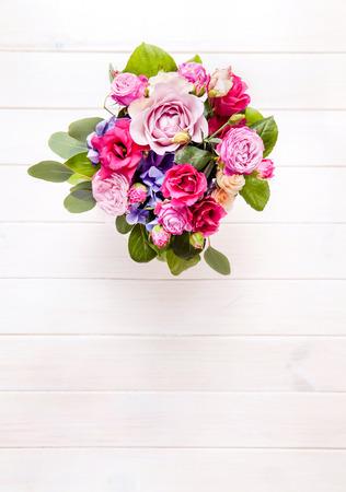 bouquet fleurs: fleurs. bouquet de roses dans un seau sur un fond en bois blanc Banque d'images