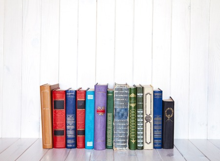 old book shelf blank spines, empty binding stack on wood texture background