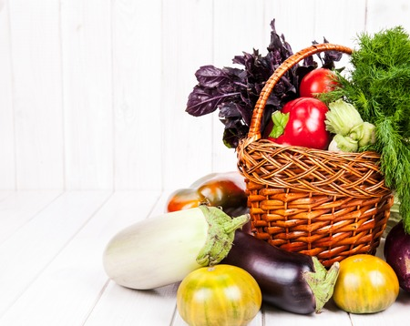 basket': Heap of fresh fruits in the basket and vegetables on wooden background