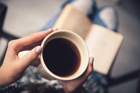 meisje met een pauze met een kopje verse koffie na het lezen van boeken of studeren