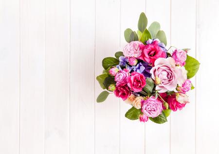 Blumen. Strauß Rosen in einem Eimer auf einem weißen hölzernen Hintergrund