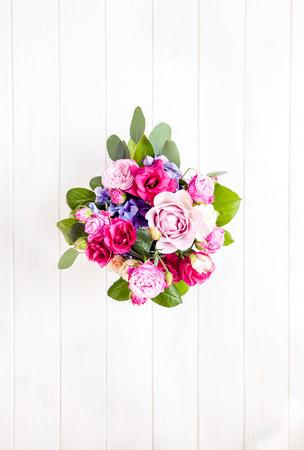 花。白い木製の背景にバケツでバラの花束 写真素材