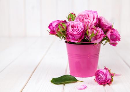 Roze rozen in vaas op een witte houten achtergrond. bloemen