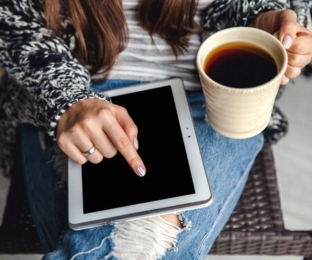 legwarmers: Soft photo of woman In the armchair with tablet and cup of coffee in hands, ripped jeans