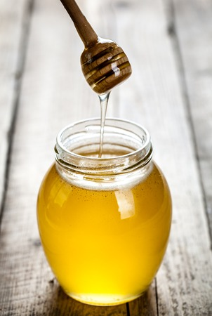 honey liquid: Honey jar with dipper and flowing honey on a wooden background