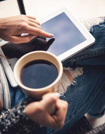 legwarmers: Soft photo of woman In the armchair with tablet and cup of coffee in hands on ripped jeans
