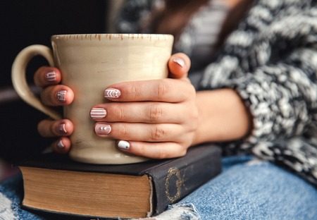 ESTUDIANDO: muchacha que tiene un descanso con una taza de café recién hecho después de la lectura de libros o estudiar