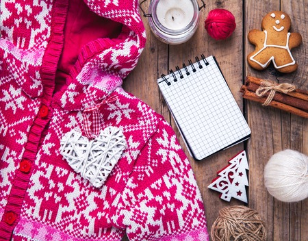 winter clothing: Christmas set. Warm blanket, sweater, candle, notebook, spices, cinnamon, pine cones, heart on the wooden background Stock Photo