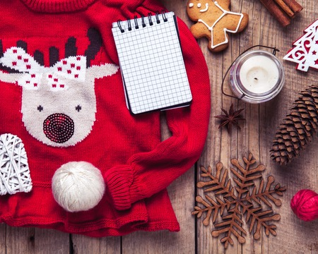 deer in heart: Christmas set. Warm blanket, sweater with a deer, candle, notebook, spices, cinnamon, pine cones, heart on the wooden background Stock Photo