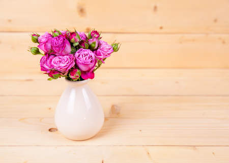 floral bouquet: Pink roses in a vase on wooden background Stock Photo