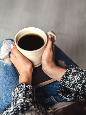 having a break: girl having a break with cup of fresh coffee after reading books or studying