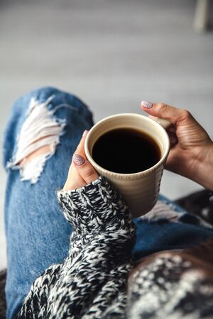 ripped jeans: Girls hands holding a cup of coffee, ripped jeans