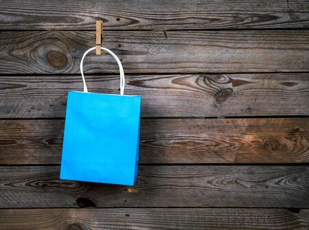 purchase: blue Shopping bag on a wooden background, sale, purchase Stock Photo