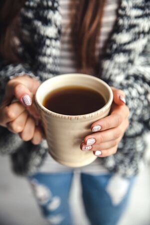 mug of coffee: Girls hands holding a cup of coffee Stock Photo