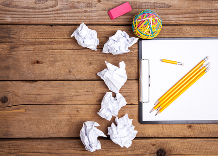 wastrel: Crumpled paper balls with pencil and clipboard on wooden background