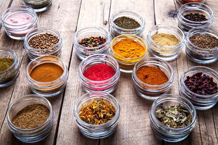 Spices in jars on wooden background. Stock Photo