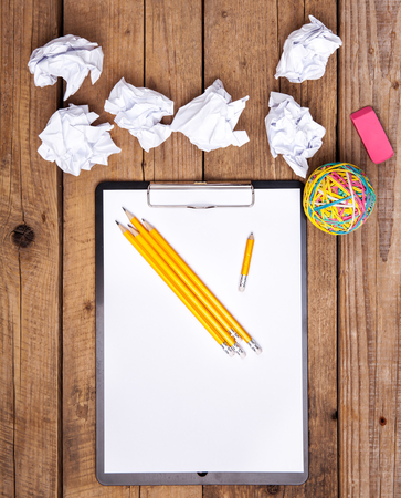 crinkly: Crumpled paper balls with pencil and clipboard on wooden background